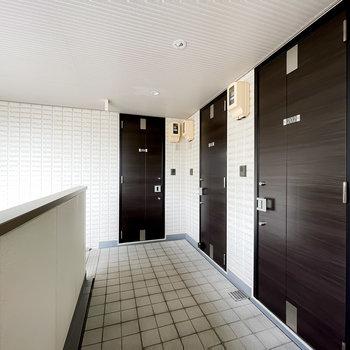 玄関前の共用部は白いタイル張りで清潔な空間。