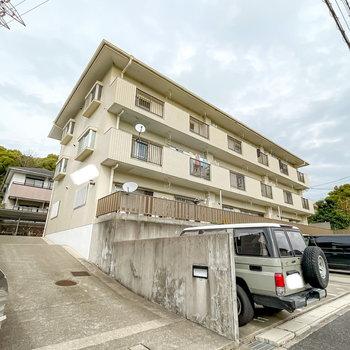 道路から少し高さのある台の上に立つ、3階建てのマンションです。