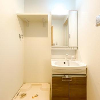 正面には鏡の大きな洗面台。洗濯機置場の上には便利な棚も付いています。