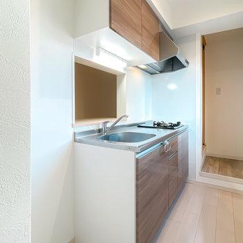 キッチンは空間に馴染む木目調。冷蔵庫置き場は左側に。