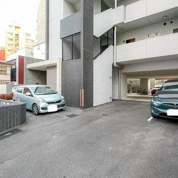 エントランス前にはゴミステーション、奥には駐車場や駐輪場があります。
