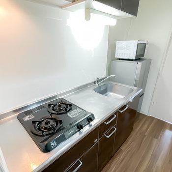コンロは2口で作業スペースも広め。冷蔵庫と電子レンジも備え付けです。