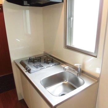 キッチンはガスコンロ2口。※写真は2階の同間取り別部屋のものです