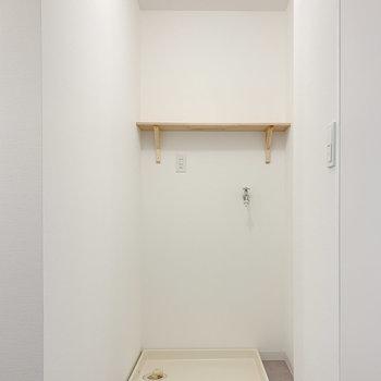 2人で使える広さの脱衣所に入ると、正面に洗濯機置場が。洗剤などを置ける木製の棚付き!