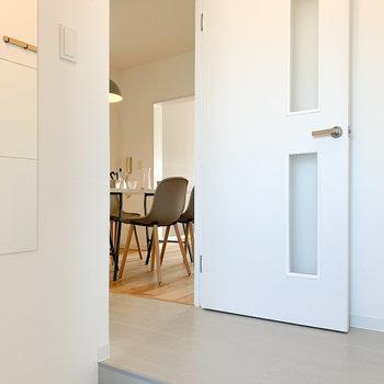 ドアを開けた瞬間から明るい、可愛らしい白いタイルの玄関。居室へ伸びる景色が素敵。
