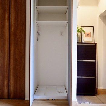 もうひとつの扉は洗濯機置き場。棚があるのも嬉しいポイント。