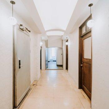 白い壁と木の扉のコントラストが美しい廊下