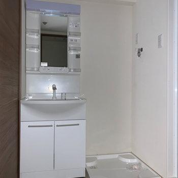 洗面台と洗濯機置き場。※通電前につきフラッシュを使用しています