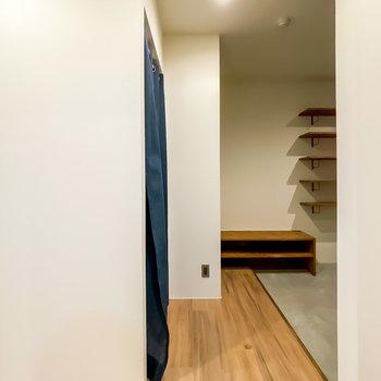 脱衣所を出ると正面に玄関が。左側にはカーテンが引いてあり……