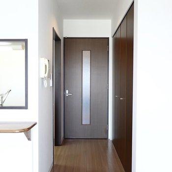通路の左にキッチン、正面に廊下へのドア。 (※写真は8階の反転間取り別部屋のものです)