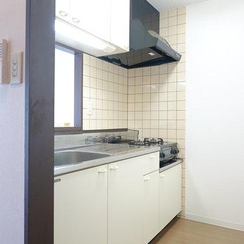 キッチンは吊戸棚付きで収納多め。 (※写真は8階の反転間取り別部屋のものです)