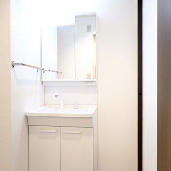 右手に綺麗な洗面台。収納ケースを置けるスペースもあります。 (※写真は8階の反転間取り別部屋のものです)