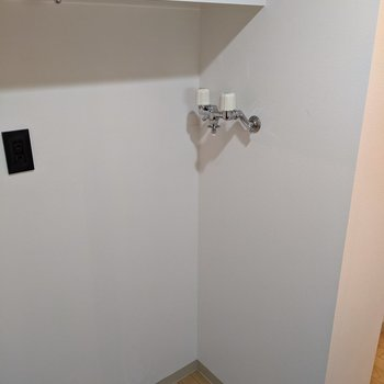洗濯機置き場があります。上には棚があるのでタオルなどを置けます。