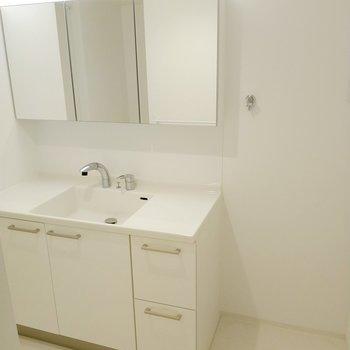 三面鏡の広々洗面台。2人並んで歯磨きできそう。洗濯機置き場は隣に。