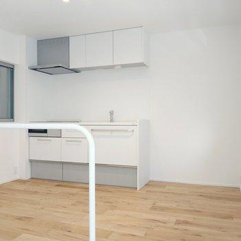 真っ白のシステムキッチン。横には換気窓も。