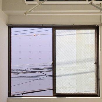 窓からの景色。道路挟んで向かいの建物の壁が見えます。