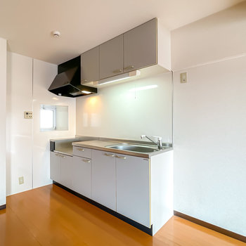 淡いパープルのキッチンは窓があり換気がしやすそう。冷蔵庫置き場はすぐ隣に。