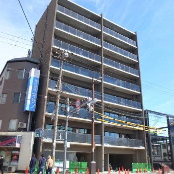 大通り沿いのマンション。青空を背負う、無彩色の外観です。
