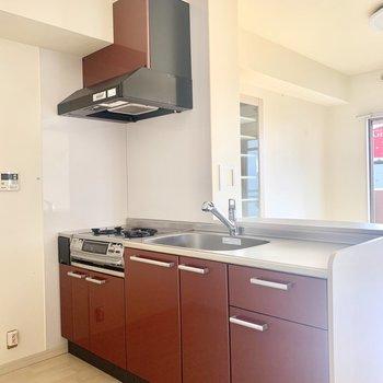 ワインレッドのキッチンがおしゃれ、、♩反対側には冷蔵庫置けます。(※写真は8階の同間取り別部屋、清掃前のものです)