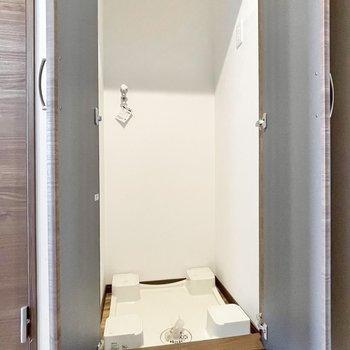 洗濯機置き場は玄関横に。扉で隠せてスッキリと◎