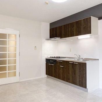 【リビング】クールな雰囲気を引き立てるのは木目調のキッチン。
