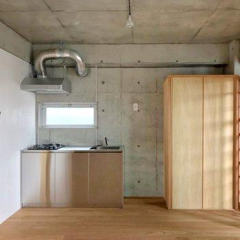 ステンレスキッチンと杉材の扉のクローゼットの組み合わせ。