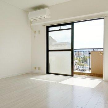 淡い木目の床に白の壁。ワンルームですが開放感があります。(※写真は8階の反転間取り別部屋のものです)