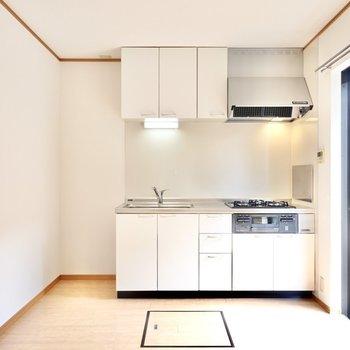 奥には壁付けキッチン。冷蔵庫置場もすぐ左に。(※写真は同間取り別部屋のものです)