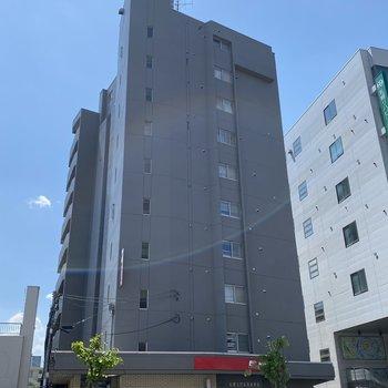 グレーの長方形の建物です。1階部分に郵便局があります。