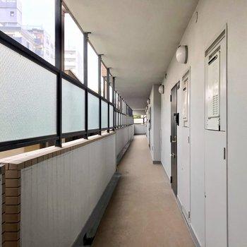 共用廊下は外に面していて明るいです。目隠しも嬉しい。