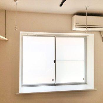 窓はスモークタイプで上には物干し掛け。