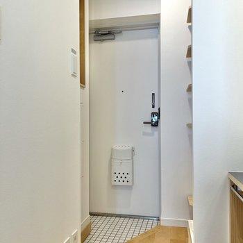 白いタイルが使われている玄関へ。
