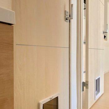 洗面台の隣にはトイレ。2枚の開き戸にはペットドアがついています。