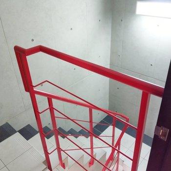 コンクリート打ちっ放しに赤の階段が映える共用階段。