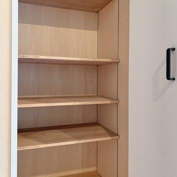 白い扉の奥に収納発見!可動式で奥行きたっぷりなので、用途に合わせて使い勝手が良いですよ。