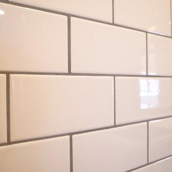 壁をクローズアップ。照り返しのある、つるんとすべすべなタイル。