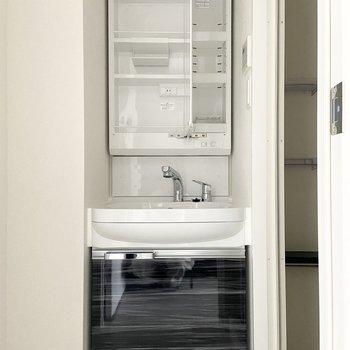 キッチンの後ろの扉はサニタリールーム。洗面台の収納は鏡の中という収納上手さ!(※写真は15階の同間取り別部屋のものです)