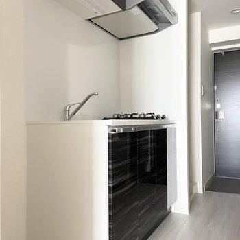 キッチンはスタイリッシュなブラック。(※写真は15階の同間取り別部屋のものです)