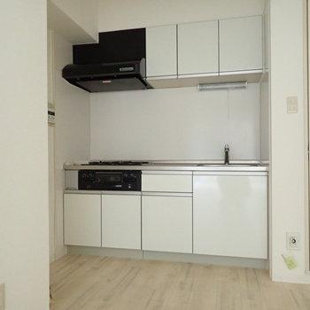 白のシステムキッチン!すみっこにおさまっています。※写真は通電前のものです