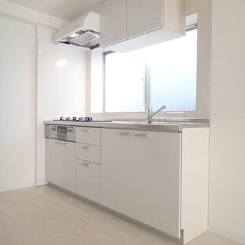 白のシステムキッチンは大きめの窓つき!