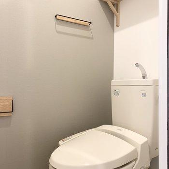 トイレはグレーのアクセントクロスで気持ち良い空間に。木製の小物たちも可愛いんだこれが。