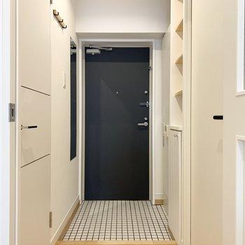 ドアを開けるとパーッと明るい白タイルの玄関がお出迎え。壁には全身鏡も付いています!