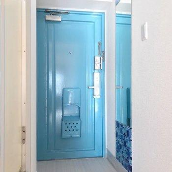 玄関はブルー。鏡にもモザイクタイルが貼られている爽やかな空間。(※写真は10階の同間取り別部屋のものです)
