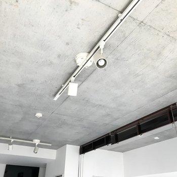 天井はコンクリ。ライティングレールと、濃いめブラウンのブラインド。(※写真は7階の同間取り別部屋、清掃前のものです)
