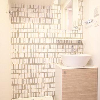 脱衣所のクロスは本棚風デザイン。洗面台もぽってりかわいらしい。(※写真は3階の同間取り別部屋のものです)