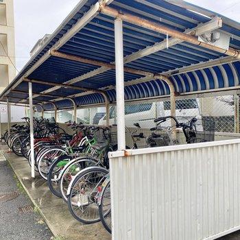 駐輪場は建物の裏側に。屋根付きで雨でびしょ濡れになる心配はなさそう。