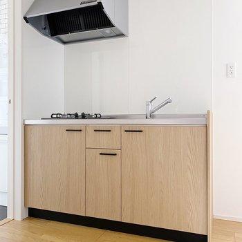 【1階】階段を下りると、木目のキッチンがあります。