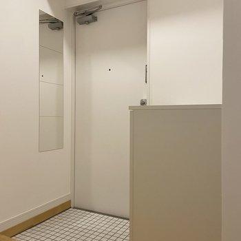 白いミニタイルが敷かれた玄関。お出かけ前は姿見で身だしなみチェック!