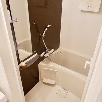 ダークブラウンの壁材がシックな浴室。