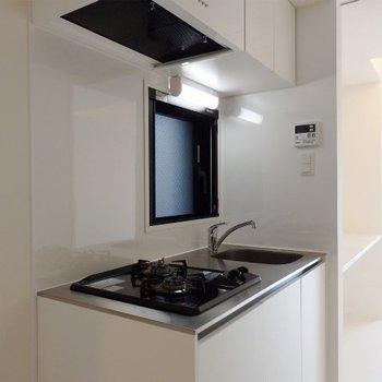 キッチンは2口コンロ。真っ白な空間に映えます(※写真は2階の同間取り別部屋のものです)
